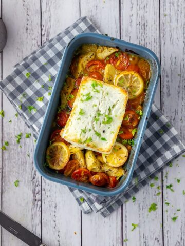Overhead shot of baked feta with vegetables in a blue baking dish on checked cloth