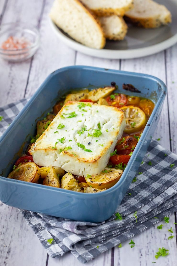 Baked feta with vegetables in a blue baking dish on a checked cloth