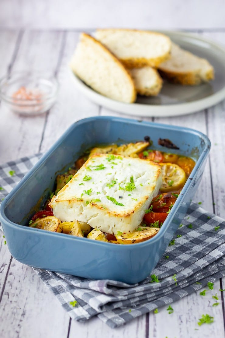 Baked feta and vegetables in a blue baking dish on a checked cloth with bread in the background