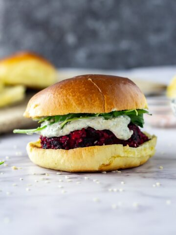 Side on shot of beetroot burger with whipped feta on a marble background