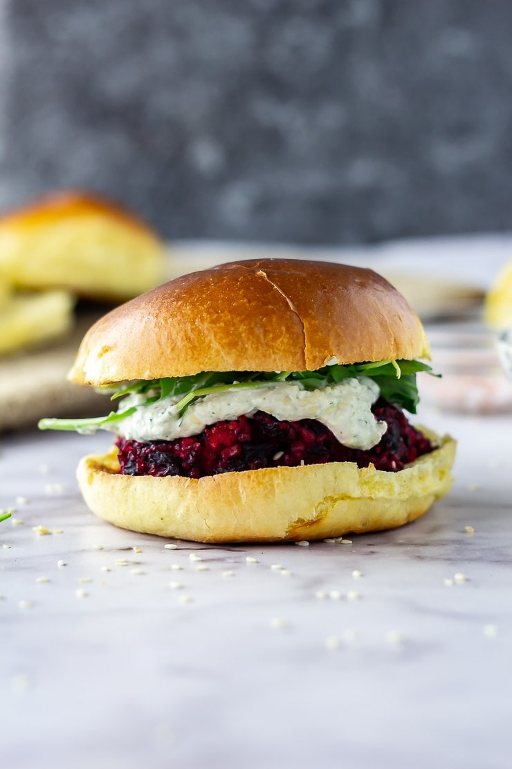 Side on shot of beetroot burgers with whipped feta on a marble background