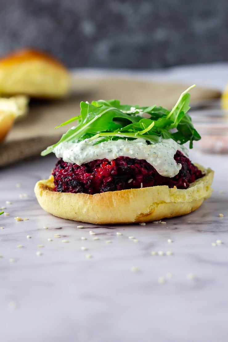 Side on shot of beetroot burgers topped with whipped feta and rocket on a marble background