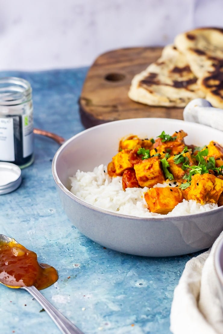 Side on shot of paneer tikka masala on a blue background with a spoonful of mango chutney