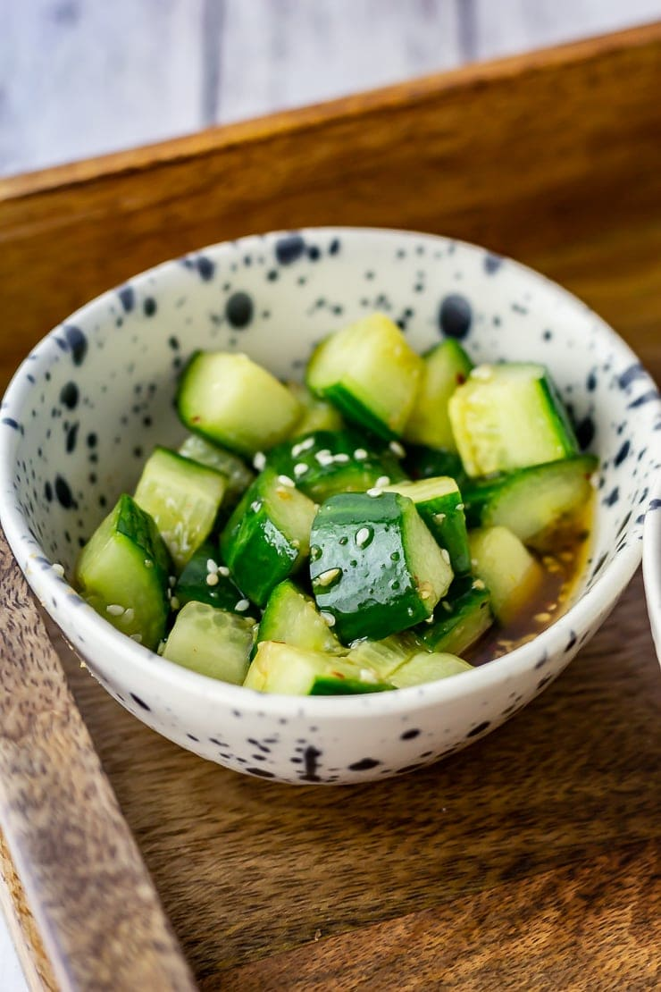 Bowl of cucumber salad in a wooden tray