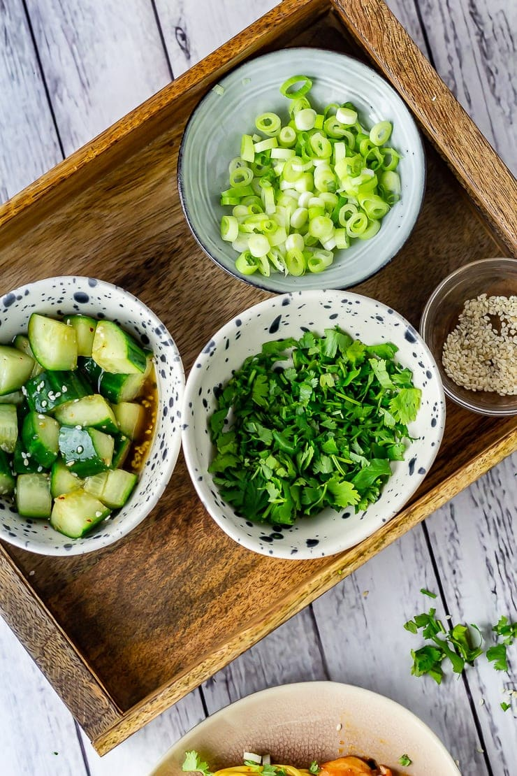 Overhead shot of a wooden tray with cucumber salad, coriander and spring onion