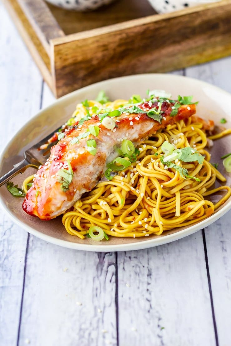 Oven cooked salmon with noodles on a plate over a white wooden background