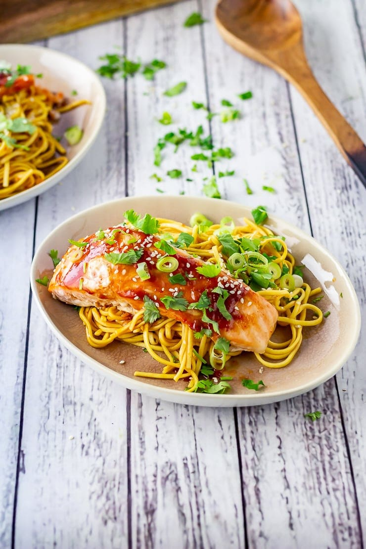 Oven cooked salmon with noodles on a plate on a white wooden background