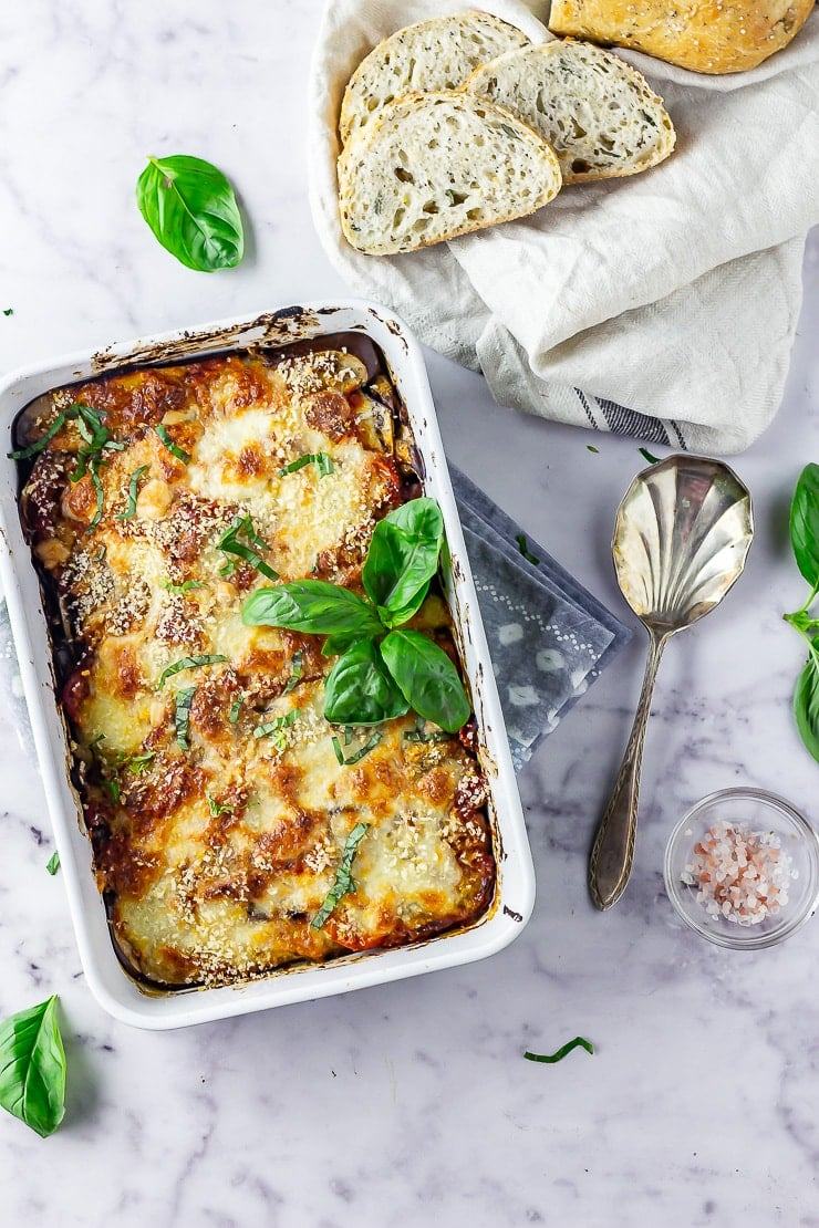 Overhead shot of aubergine parmigiana on a marble background with bread