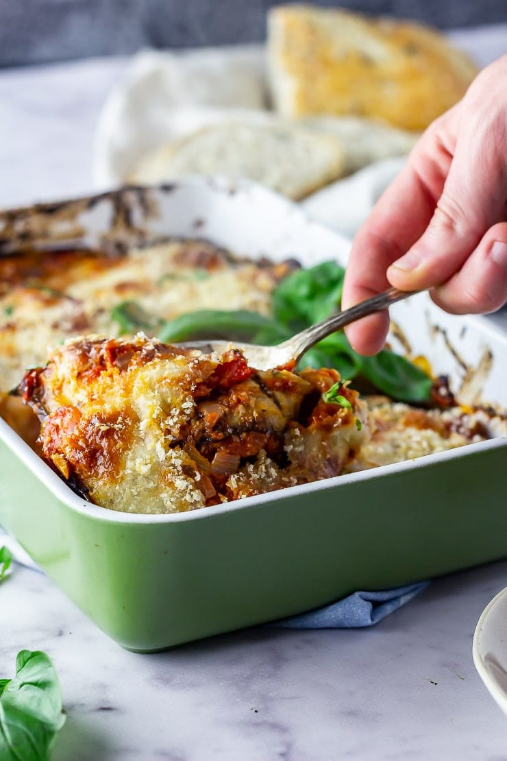 Aubergine parmigiana in a green baking dish with a spoonful being taken