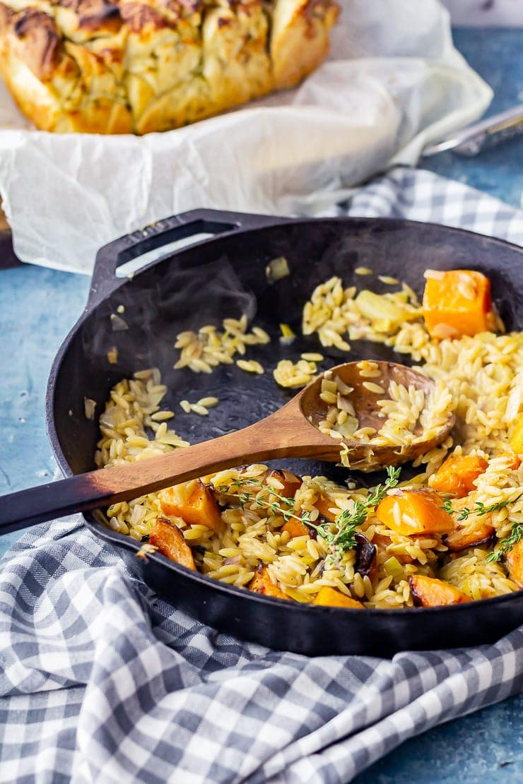 One pot orzo with roasted butternut squash in a cast iron skillet on a checked cloth