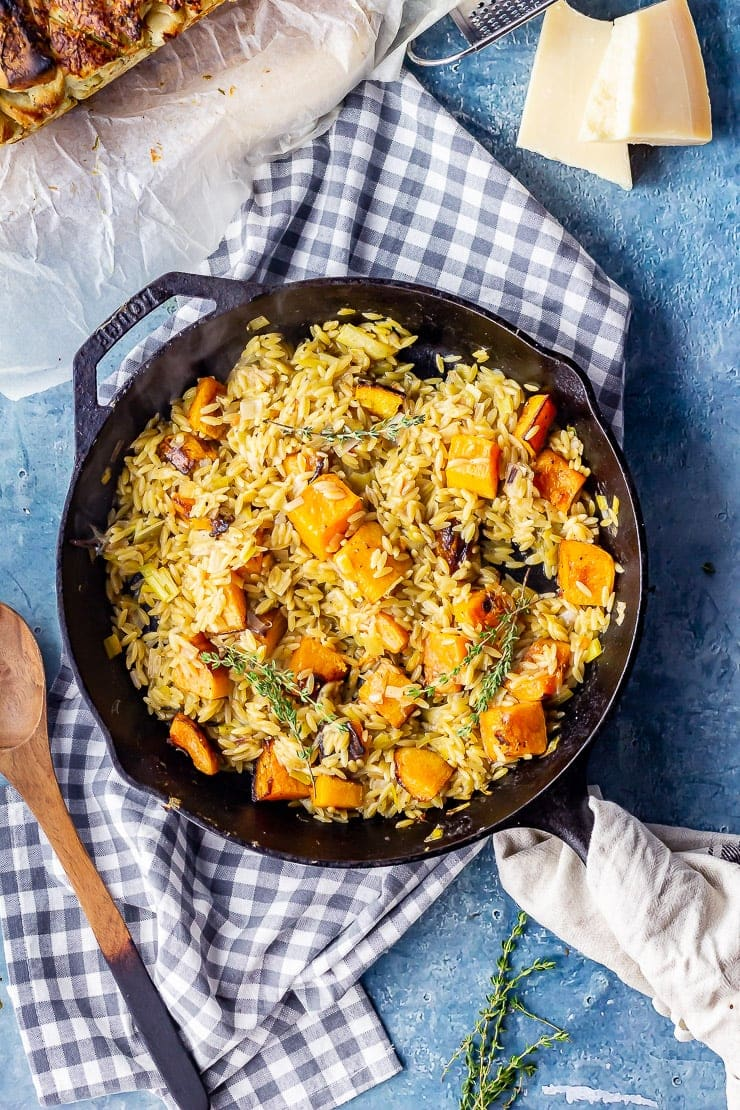Overhead shot of one pot orzo with roasted butternut squash on a checked cloth over a blue background
