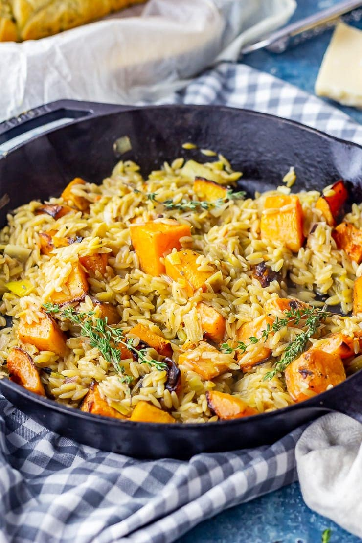 One pot orzo with butternut squash in a skillet on a checked cloth