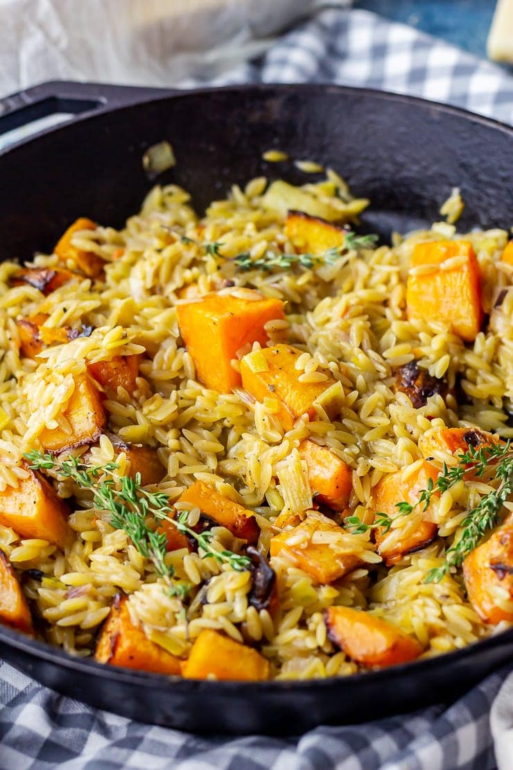 Close up of one pot orzo with roasted butternut squash on a checked cloth