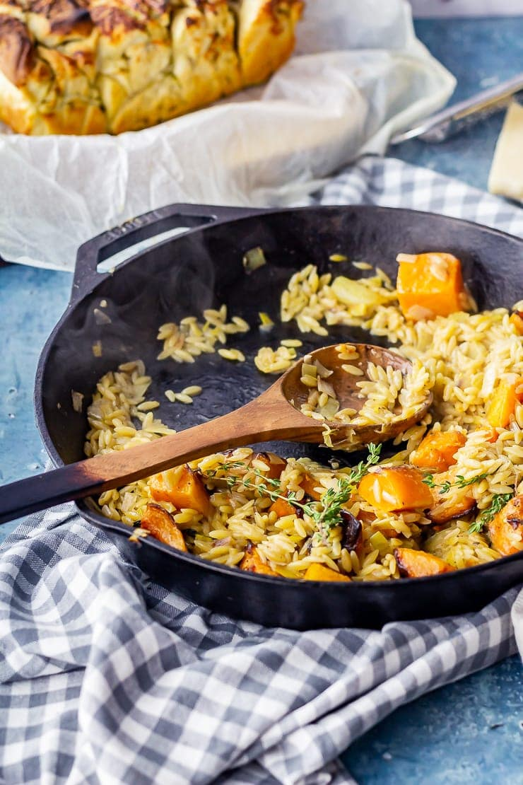 One pot orzo with butternut squash with a wooden spoon and checked cloth