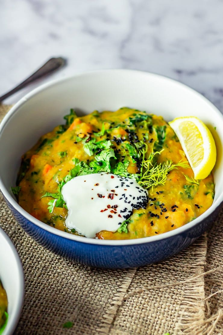 Bowl of lentil stew with yoghurt on top over a marble background