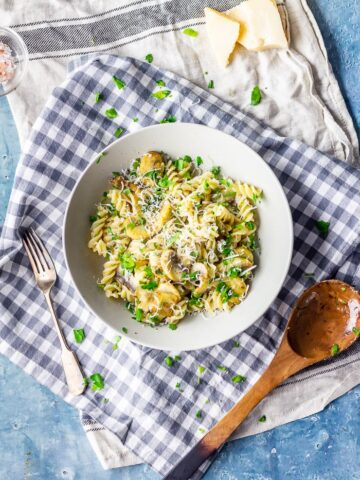 Overhead shot of garlic mushroom pasta on a checked cloth with a wooden spoon and a blue background