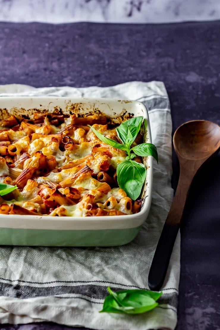 Side on shot of cheese and tomato pasta bake on a cloth with a wooden spoon