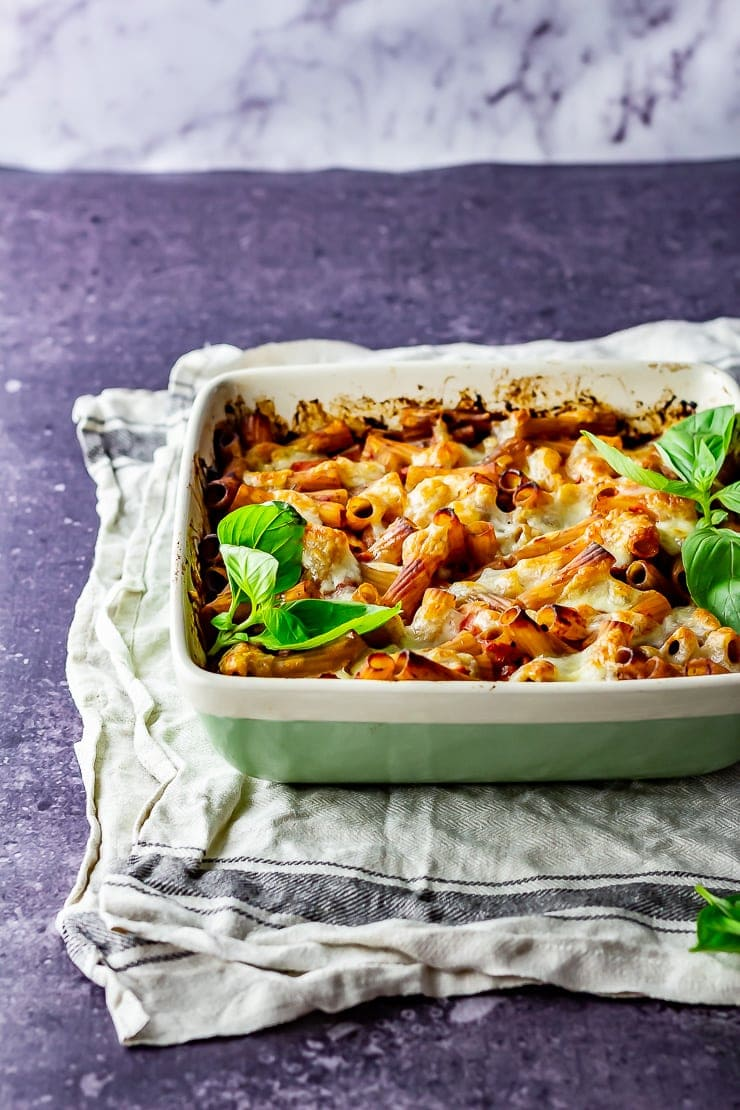Side on shot of cheese and tomato pasta bake on a cloth with a grey background