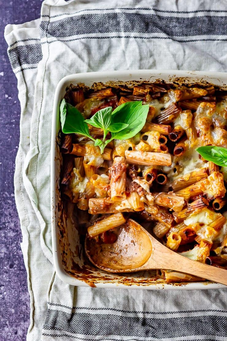 Overhead shot of cheese and tomato pasta bake with a wooden spoon