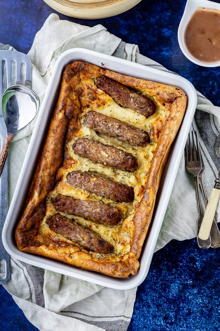 Overhead shot of vegetarian toad in the hole on a cloth over a blue background