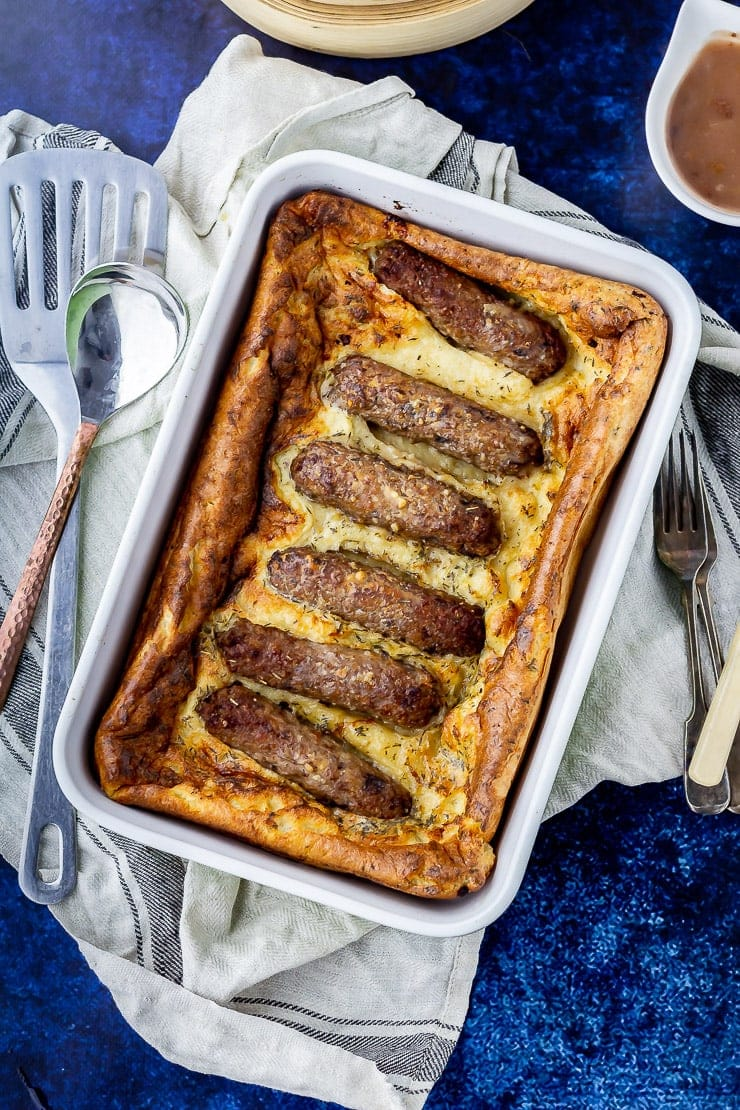 Overhead shot of vegetarian toad in the hole over a pale cloth on a dark blue background