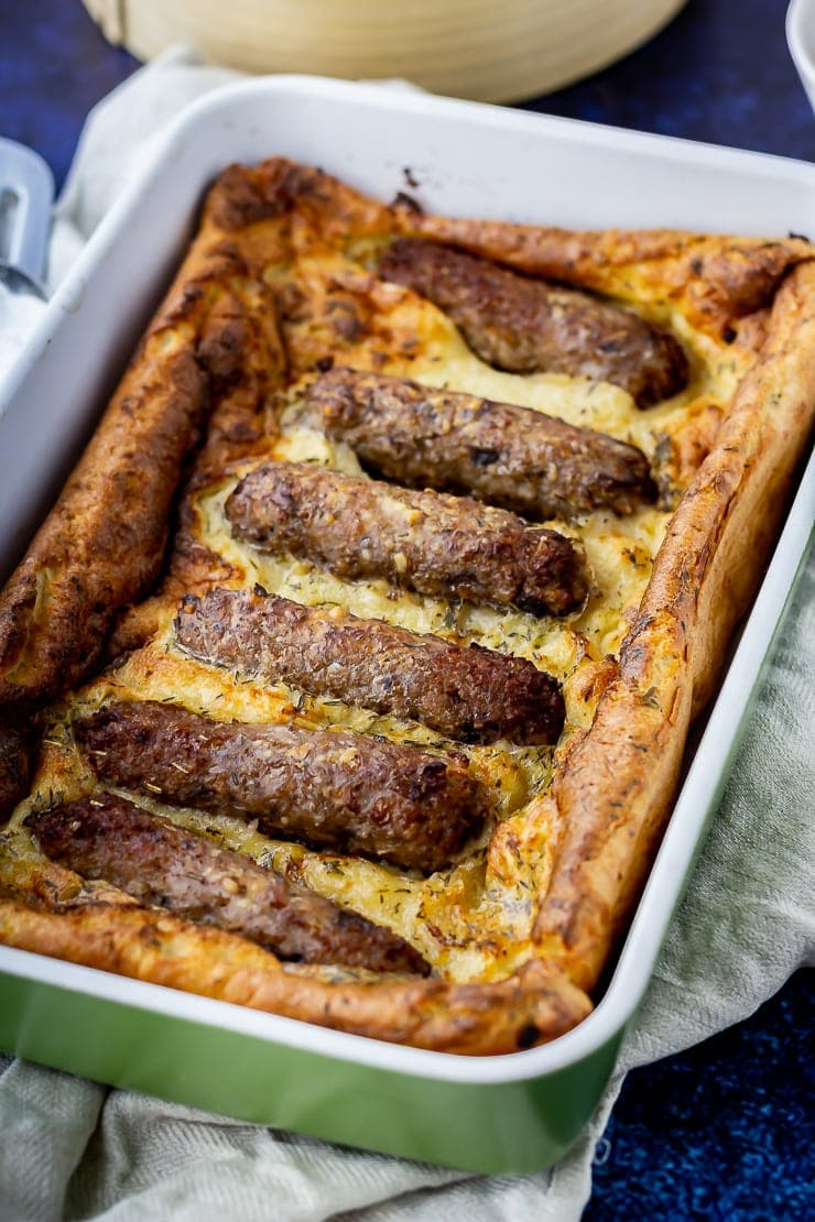 Green baking dish with vegetarian toad in the hole on a cloth