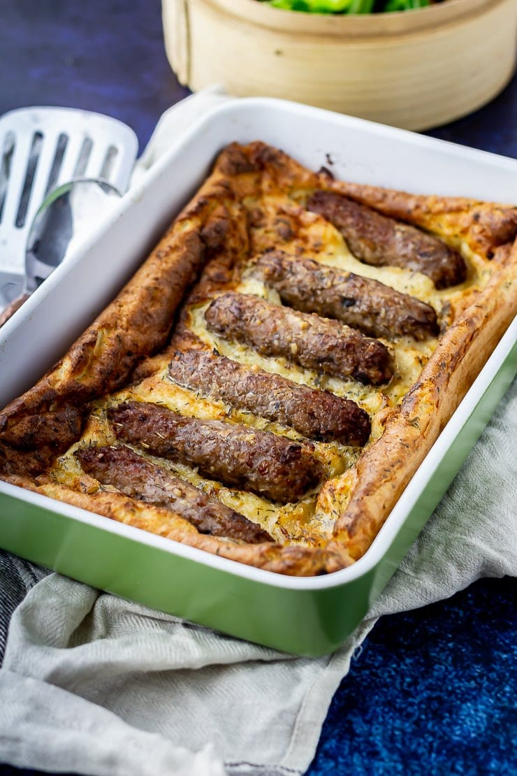 Green baking dish with vegetarian toad in the hole in a pale cloth