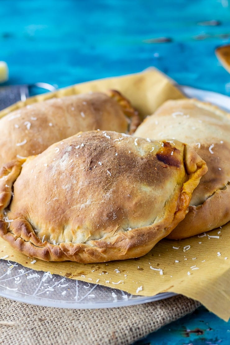 Three roasted vegetables calzones on a plate covered in paper on a blue background
