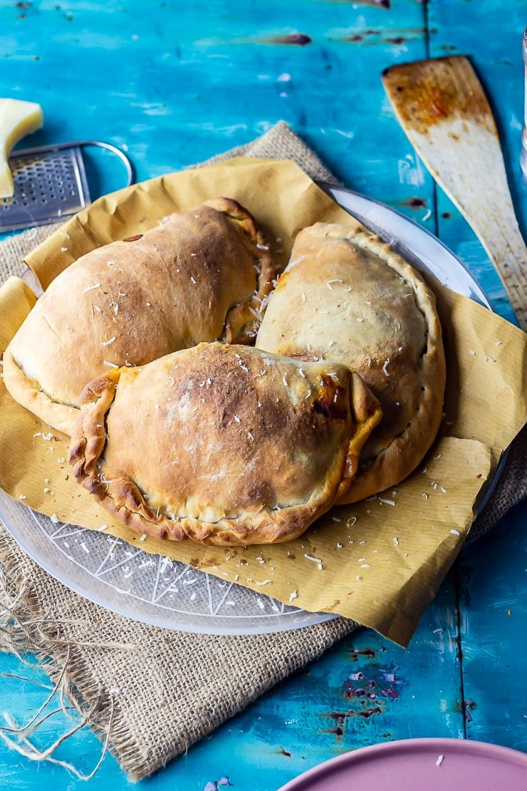 Roasted vegetable calzones on paper over a plate