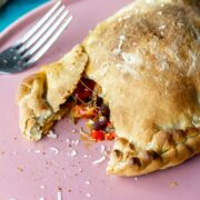 Pink plate with a roasted vegetable calzone and a fork