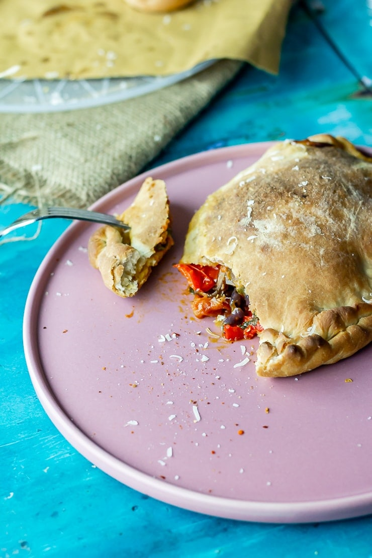 Roasted vegetable calzone on a pink plate with a fork taking a bite