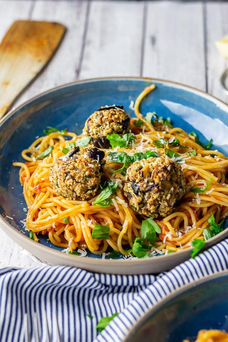 Blue bowl of vegetarian spaghetti and meatballs with a striped cloth