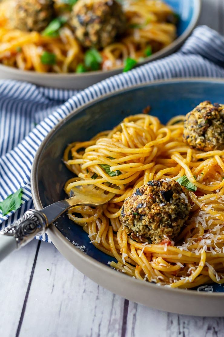 Vegetarian spaghetti and meatballs with a fork on a white wooden background