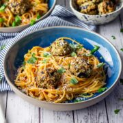 Vegetarian spaghetti and meatballs in a blue bowl on a white wooden background