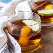 Side on shot of spiced apple cocktail with rum in a mat with a cloth