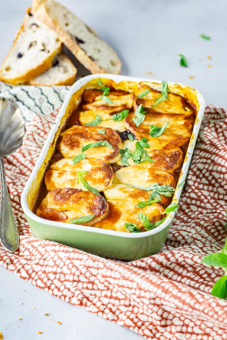 Side angle shot of halloumi bake in a green baking dish