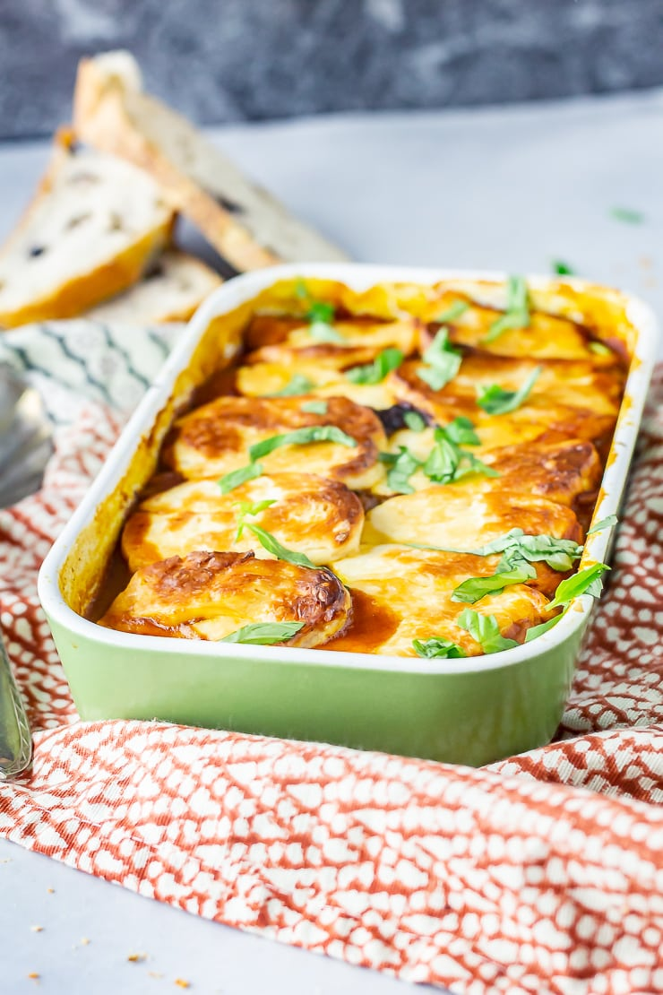 Side angle shot of halloumi bake in a green baking dish on a patterned cloth