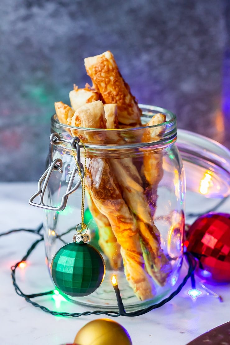 Side angle shot of chipotle cheese twist in a glass jar with Christmas decorations