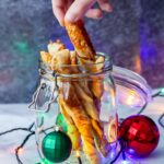 Side on shot of chipotle cheese twists in a glass jar with a hand taking one and Christmas decorations