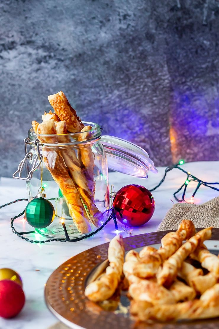 Side on shot of chipotle cheese twists on a platter and in a glass jar with Christmas decorations