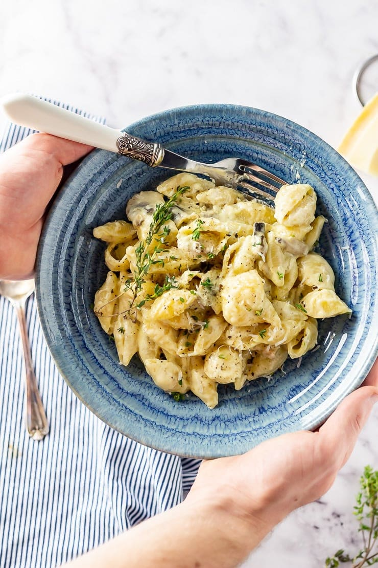 20 Minute Dinners: Overhead shot of hands holding a blue bowl of creamy mushroom pasta