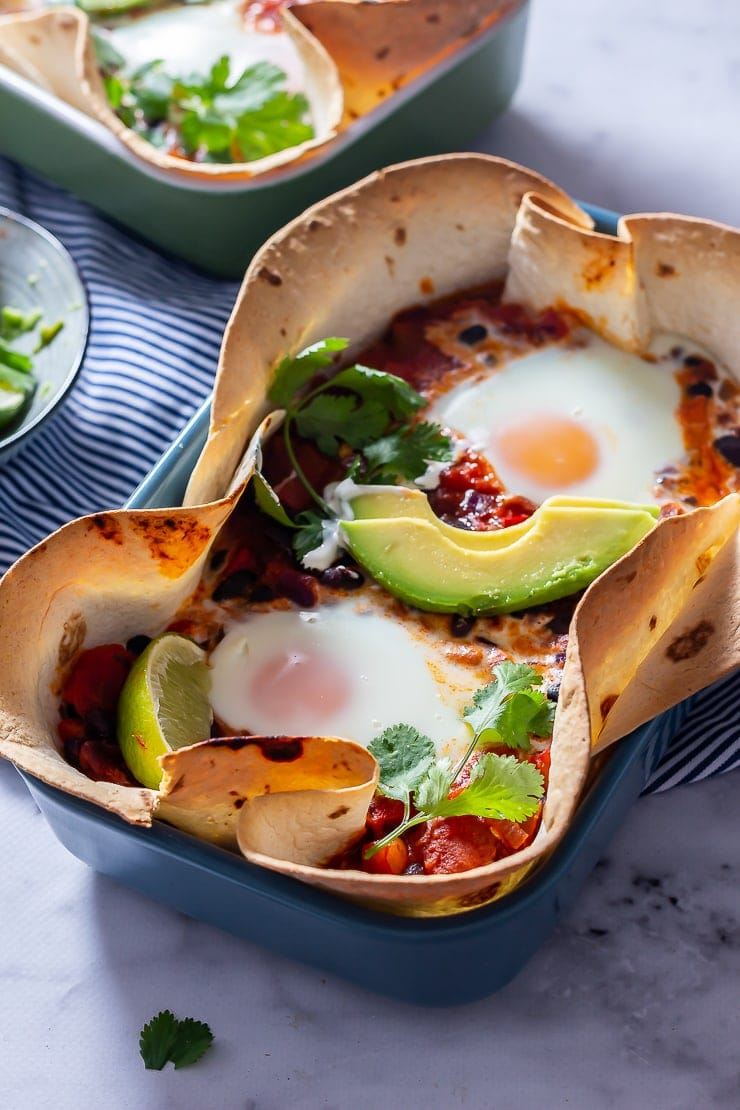 Side angle shot of huevos rancheros baked eggs in a blue dish on a marble background
