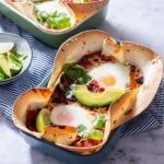 Side angle shot of huevos rancheros baked eggs on a marble background