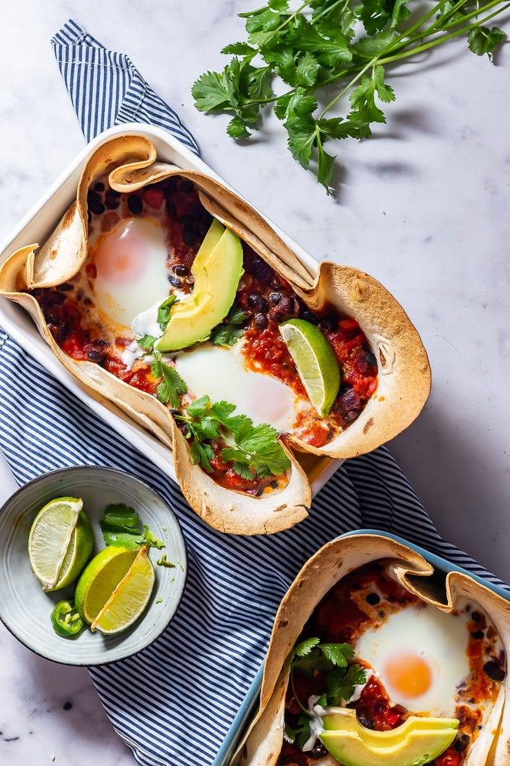 Overhead shot of huevos rancheros baked eggs on a striped cloth and a marble background