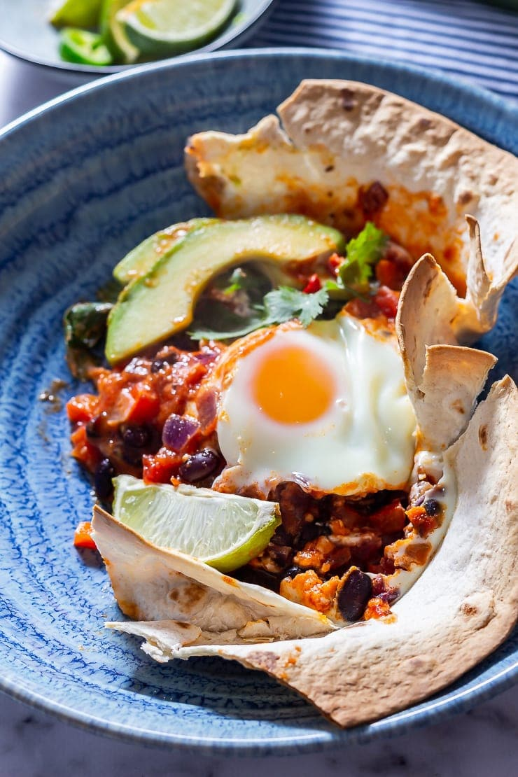 Portion of huevos rancheros baked eggs in a blue bowl