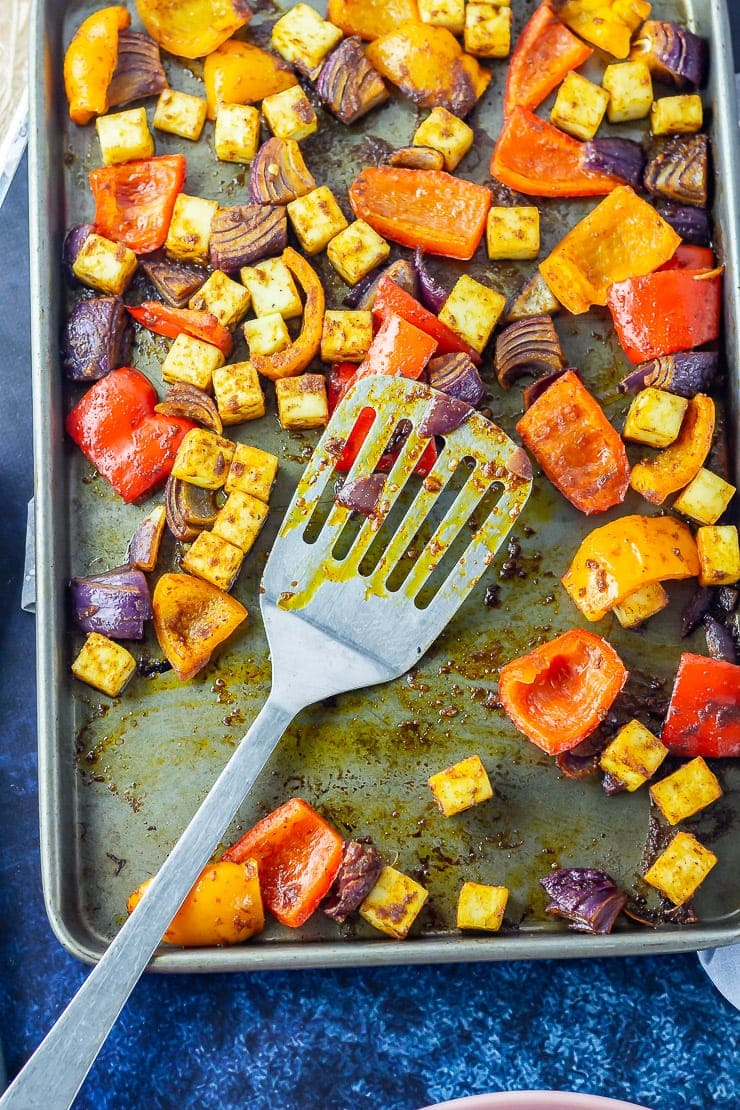 Overhead shot of chilli paneer tray bake with a spatula