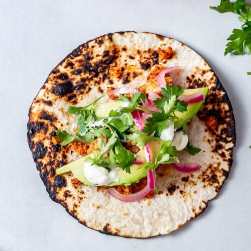 Overhead shot of salmon tacos on a grey background with pickled red onions