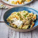 Leftover turkey pilaf in a blue bowl on a white wooden background