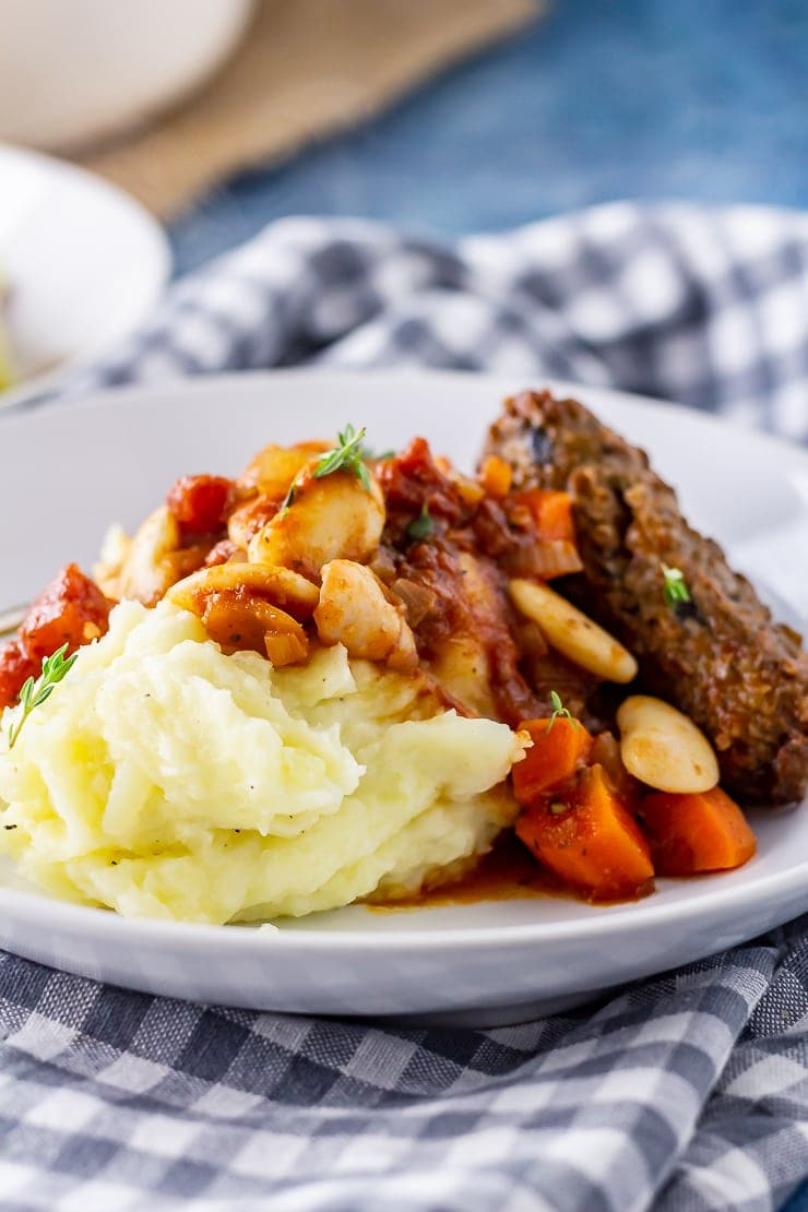 Side angle shot of vegetarian sausage casserole with mashed potato in a white bowl