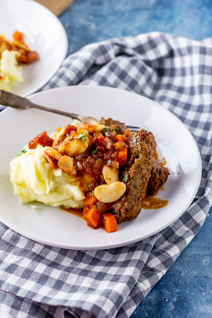 White plate of vegetarian sausage casserole with mash on a checked cloth